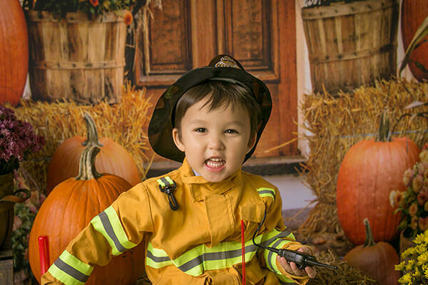 Little boy wearing a fireman costume in a pumpkin patch in need of emergency dental services from Children's Dentistry of DuPont