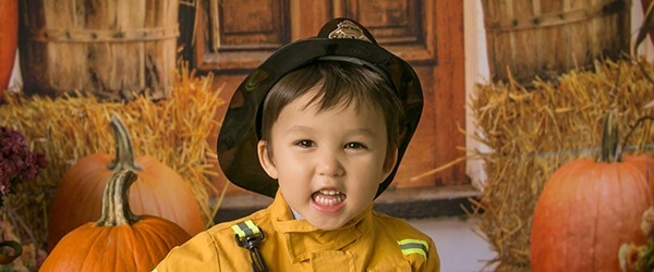 Picture of child in pumpkin patch with fireman suit on